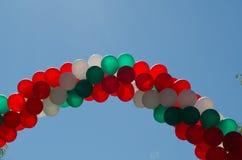 在蓝天的气球曲拱在意大利颜色的绿色白色和红色 库存照片