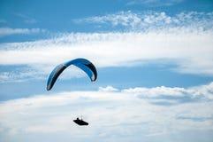 在蓝天的滑翔伞飞行以云彩为背景 免版税库存图片