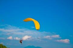 在蓝天的滑翔伞 免版税库存照片