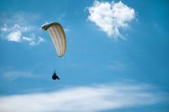 在蓝天的白色滑翔伞飞行以云彩为背景 库存照片