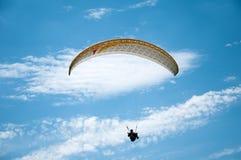 在蓝天的白色滑翔伞飞行以云彩为背景 免版税库存照片