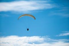 在蓝天的白色滑翔伞飞行以云彩为背景 免版税库存图片