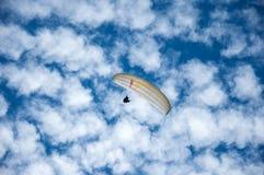 在蓝天的白色滑翔伞飞行以云彩为背景 图库摄影