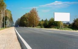 在蓝天的空白的广告牌与高速公路 免版税图库摄影