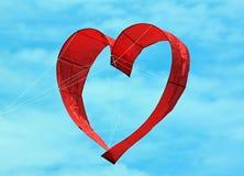 在蓝天的红色心脏风筝 免版税库存照片