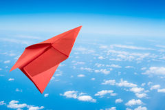 在蓝天的红色纸飞机, 库存照片