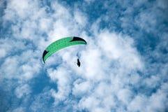 在蓝天的绿色滑翔伞飞行以云彩为背景 免版税库存照片