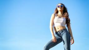 在蓝天的美丽的少妇 免版税图库摄影