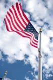 绞在蓝天的美国国旗 图库摄影