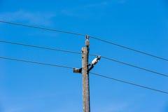 在蓝天的老简单的农村木电子杆 库存图片