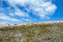 在蓝天的老破旧的石篱芭 免版税库存图片