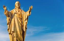 在蓝天的耶稣基督金黄雕象 图库摄影