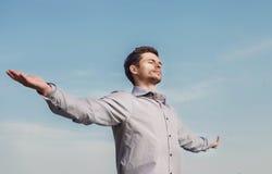 在蓝天的镇静年轻人画象 免版税库存图片