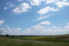 在蓝天的长篇白色云彩,美好的夏天风景,领域在村庄 库存图片