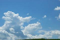 在蓝天的长篇白色云彩,美好的夏天风景,领域在村庄 免版税库存照片
