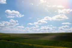 在蓝天的长篇白色云彩,美好的夏天风景,领域在村庄 库存照片