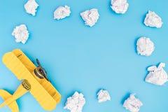 在蓝天的黄色玩具飞机与与拷贝空间的纸云彩 免版税库存照片