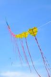 在蓝天的黄色风筝 免版税库存图片