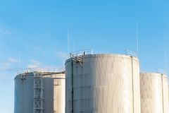 在蓝天背景的三个汽油桶 存贮在里加 免版税库存图片