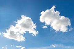 在蓝天背景的两朵白色云彩 库存图片