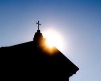 在蓝天背景的宗教十字架在阳光下 免版税库存图片