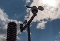 在蓝天背景的家庭气象台与太阳的在云彩后 温度、湿气和风dir的测量 免版税库存图片