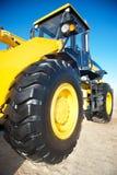 在蓝天背景的明亮的黄色拖拉机  库存照片