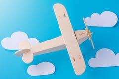 在蓝天背景的木玩具飞机与纸云彩的 概念旅行和航空公司 图库摄影