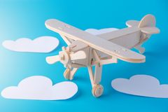 在蓝天背景的木玩具飞机与纸云彩的 概念旅行和航空公司 库存照片