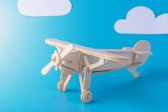 在蓝天背景的木玩具飞机与纸云彩的 概念旅行和航空公司 免版税图库摄影