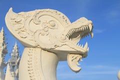 在蓝天背景的白色半狮子和龙顶头雕塑 免版税图库摄影