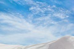 在蓝天背景的白色随风飘飞的雪与云彩的 图库摄影