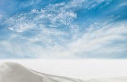 在蓝天背景的积雪的领域与云彩的 库存图片