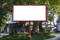 在蓝天背景的空白的红色广告牌新的广告的在城市 免版税库存图片