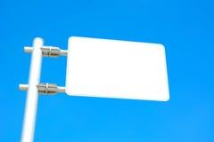 在蓝天背景的空白的路标板 库存图片
