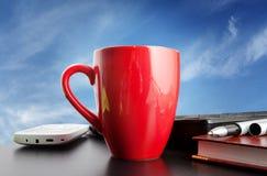 在蓝天背景的红色杯子  免版税库存照片