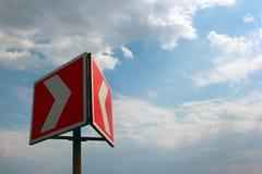 在蓝天背景的红色白色警告箭头 库存图片