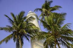 在蓝天背景的老灯塔由棕榈围拢 库存照片