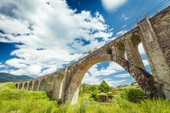 在蓝天背景的老石桥梁  免版税库存照片