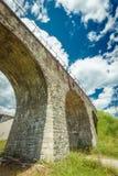 在蓝天背景的老石桥梁  免版税库存图片
