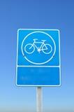 在蓝天背景的蓝色停车自行车符号。 免版税库存图片