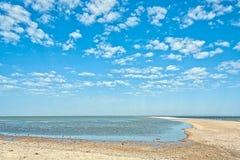 在蓝天背景的离开的海滩与云彩的 库存照片