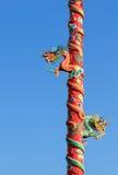 在蓝天背景隔绝的红色柱子的两条龙 库存照片