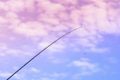 在蓝天,云彩被定调子的背景的钓鱼竿  复制空间 库存照片
