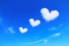 在蓝天,爱概念的三朵白色心形的云彩 库存照片