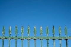 在蓝天-葡萄酒加工的金属钉的老铁篱芭- 免版税图库摄影