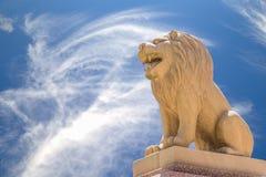 在蓝天backgroung的被雕刻的砂岩狮子 免版税图库摄影