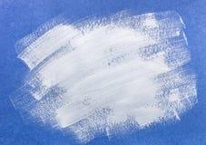 在蓝纸的传神画笔冲程 图库摄影