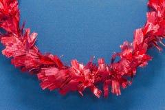 在蓝纸的红色丝带背景的 图库摄影