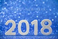 在蓝纸的2018个白色木数字与闪烁点燃 免版税库存图片